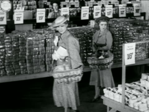 B/W 1938 2 women carrying baskets shopping in grocery store / industrial