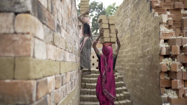 Women carrying bricks on her head