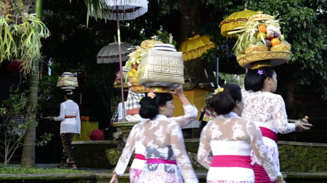 ms women carrying offerings on her head in colorful decorated pura dalem puri temple / ubud, bali, indonesia - ubud district stock videos & royalty-free footage