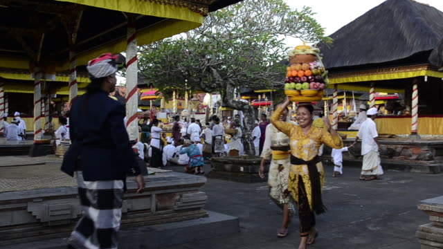 vidéos et rushes de ms ts women carrying offerings on her head in pura dalem puri temple / ubud, bali, indonesia - coiffe traditionnelle