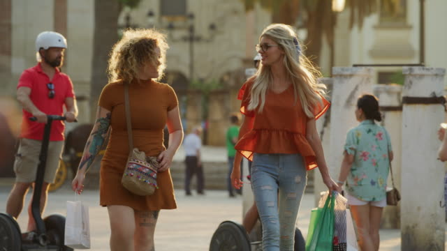 women carrying shopping bags walking and laughing in city / seville, sevilla, spain - borsetta video stock e b–roll