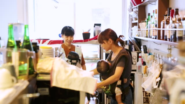 women carrying their baby working at cafe - working mother stock videos & royalty-free footage