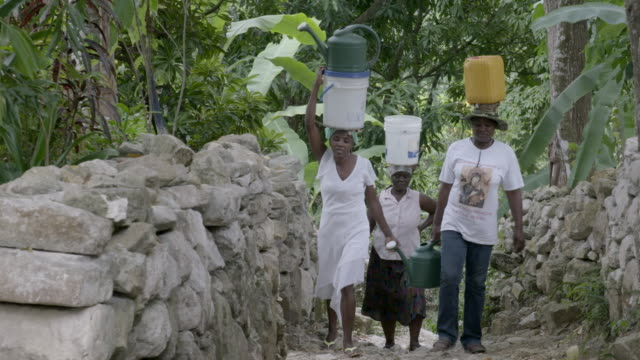 Women carrying water on their heads after 2010 earthquake NO