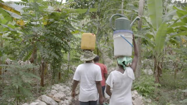 stockvideo's en b-roll-footage met women carrying water on their heads - haïti