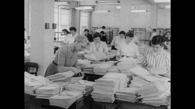 1960 women census takers go through stacks and stacks of documents - form document stock videos and b-roll footage