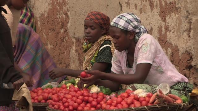 women chat as they sell produce at a local market in rural rwanda - ルワンダ点の映像素材/bロール