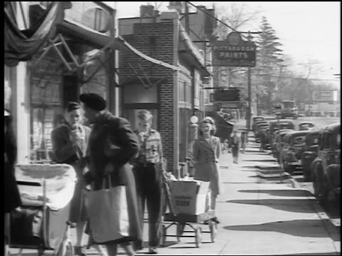 vídeos de stock e filmes b-roll de b/w 1943/44 women, children + teens walk on town sidewalk / some eat ice cream cones, pull wagons - nova jersey