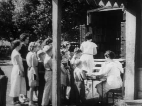 b/w 1934 women children waiting in line to enter bookmobile on street / newsreel - anno 1934 video stock e b–roll
