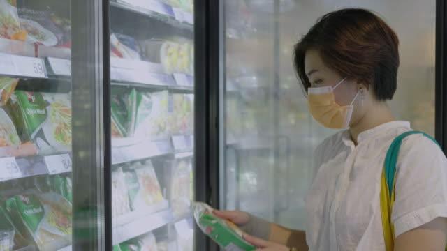 stockvideo's en b-roll-footage met vrouwen kiezen ervoor om bevroren voedsel te kopen in de supermarkt. - dairy product