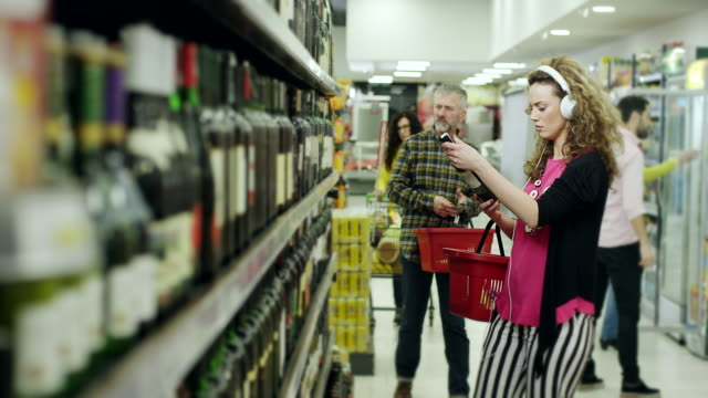 vídeos de stock, filmes e b-roll de mulheres escolher a garrafa de vinho e ouvindo música em fones de ouvido no supermercado - escolhendo