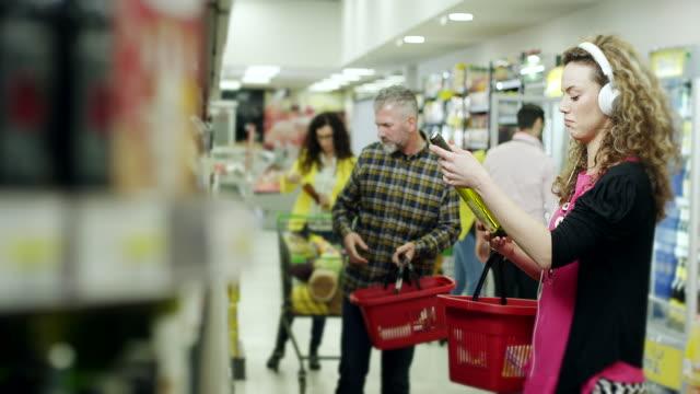 vídeos y material grabado en eventos de stock de mujeres elegir la botella de vino y escuchar música con auriculares en supermercado - super slow motion