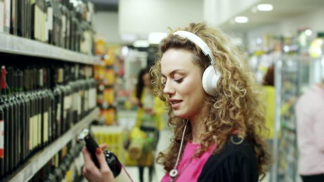 vídeos de stock e filmes b-roll de women choosing bottle of wine and listening music on headphones in supermarket - escolha