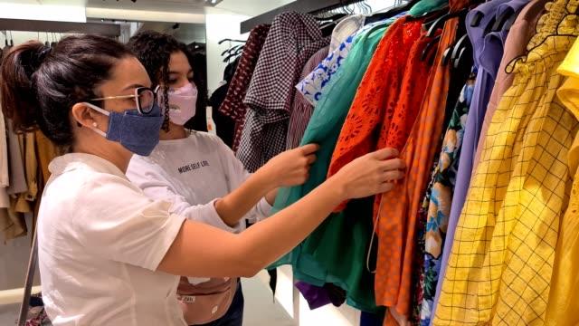 vídeos y material grabado en eventos de stock de mujeres eligiendo ropa en la tienda durante una pandemia de coronavirus - boutique