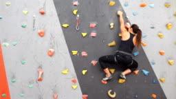 Women climbing on a wall in an outdoor climbing center
