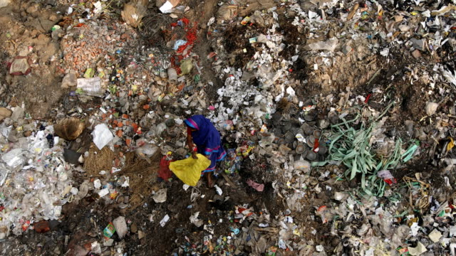 women collect usable plastics from plastic garbage. zakir hossain chowdhury/getty images the commingling point of the rivers buriganga and bangshi in... - slum stock videos & royalty-free footage