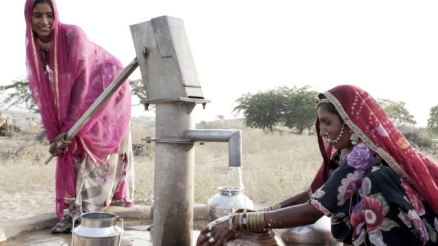 women collecting clean water in rajasthani desert. - water pump stock videos & royalty-free footage