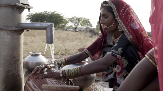women collecting clean water in rajasthani desert. - fame video stock e b–roll