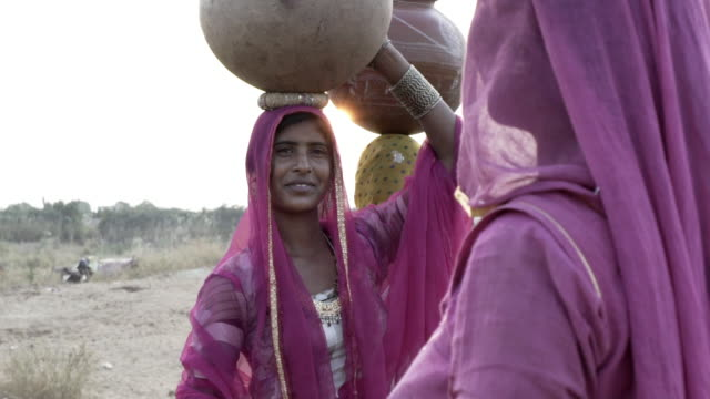 women collecting clean water in rajasthani desert. - rajasthan stock videos and b-roll footage
