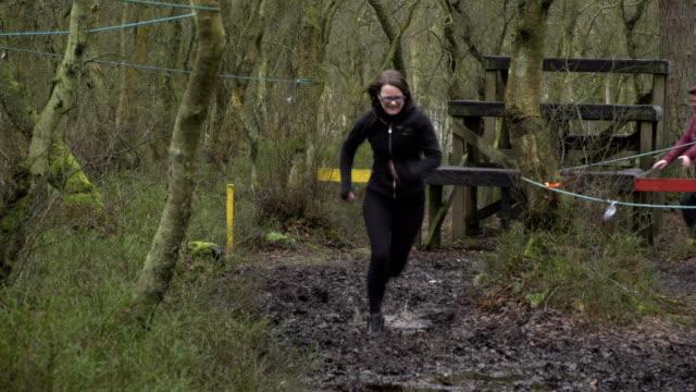 4K: Women competing in Mud Run through woodland