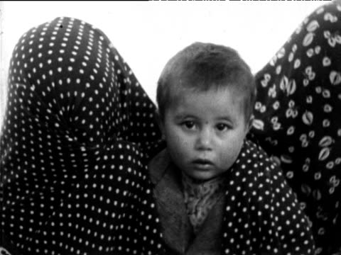 women completely wrapped in veils two small children looking at the camera tehran 1963 - teheran stock-videos und b-roll-filmmaterial