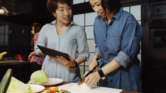 Women Cooking and looking at Tablet Computer