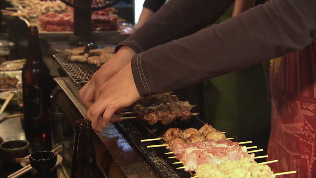 CU ZO MS Women cooking yakitori in restaurant, Tokyo, Japan