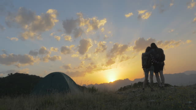 Women couple looking at sunset on the top of a mountain