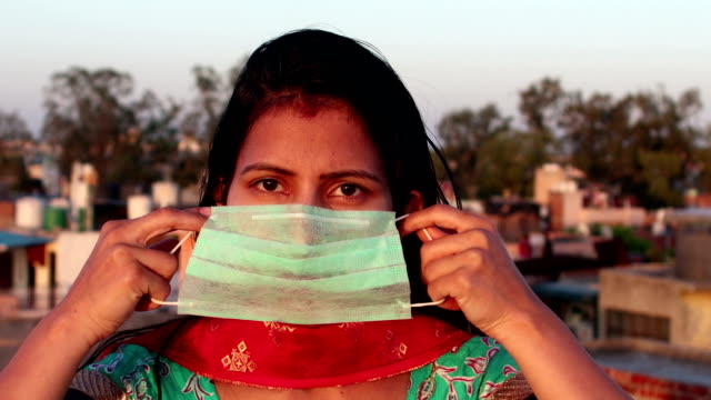 Women covering her face with pollution mask for protection from viruses