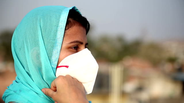 women covering her face with pollution mask for protection from covid-19 - hand on chin stock videos & royalty-free footage
