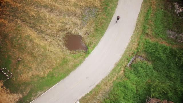 vídeos de stock, filmes e b-roll de mulheres ciclismo em estrada rural - seguindo