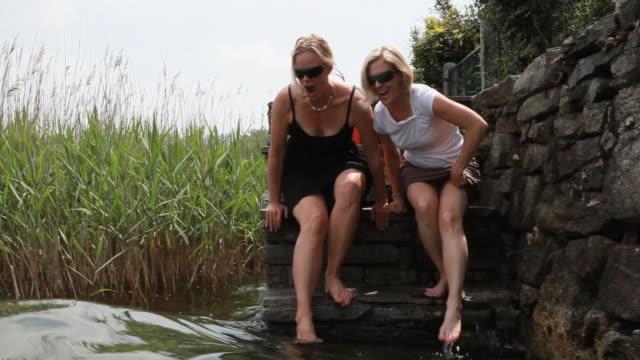 vídeos de stock, filmes e b-roll de as mulheres dabble seus pés na lagoa das etapas de pedra - 55 59 anos