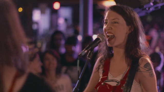 vidéos et rushes de women dance and cheer in the front row as a girl band plays in a crowded rock club - instrument de musique