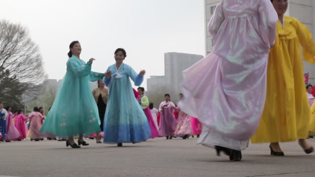 women dance in the streets to celebrate the 100th anniversary of the birth of president kim jong il in pyongyang, north korea. - north korea stock videos & royalty-free footage