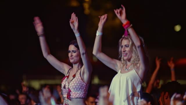 vídeos de stock e filmes b-roll de women dancing on men's shoulders at concert - cantar
