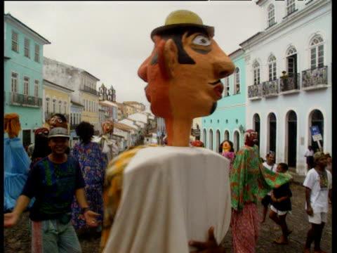 vídeos y material grabado en eventos de stock de women dancing with men in large masks and costumes at salvador street carnival - bahía