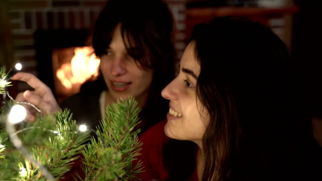 vidéos et rushes de women decorating a christmas tree with a fireplace behind - allumer