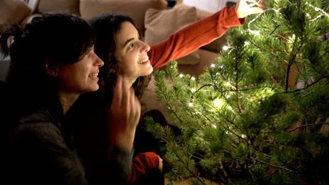 vídeos de stock e filmes b-roll de women decorating a christmas tree with a fireplace behind - luz led