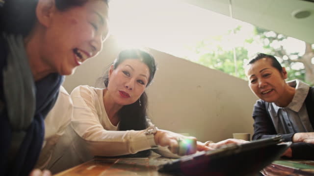 women delighted by tablet game - discussion点の映像素材/bロール