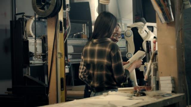 women designer working on powered exoskeleton project in wood workshop - exoskeleton stock videos & royalty-free footage