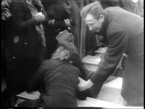 women display bandages and numbered identification tattoos on their arms / dead bodies lying on ground / women weep / german civilians recovering... - prisoner of war stock videos & royalty-free footage