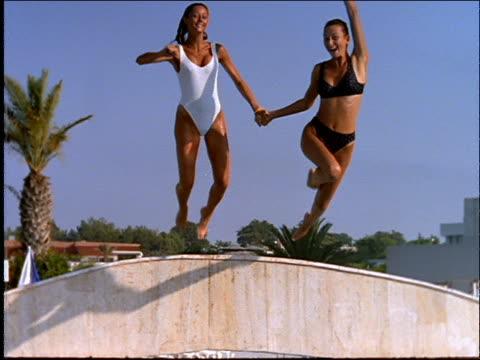 women diving from bridge into swimming pool - bikini stock videos and b-roll footage