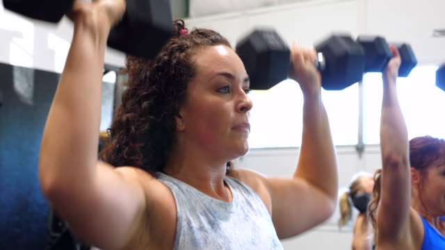ms women doing dumbbell presses during fitness class in gym - standing stock videos & royalty-free footage