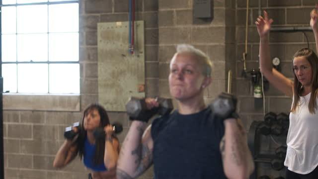 women doing dumbbell squats during fitness class in gym - sich verschönern stock-videos und b-roll-filmmaterial
