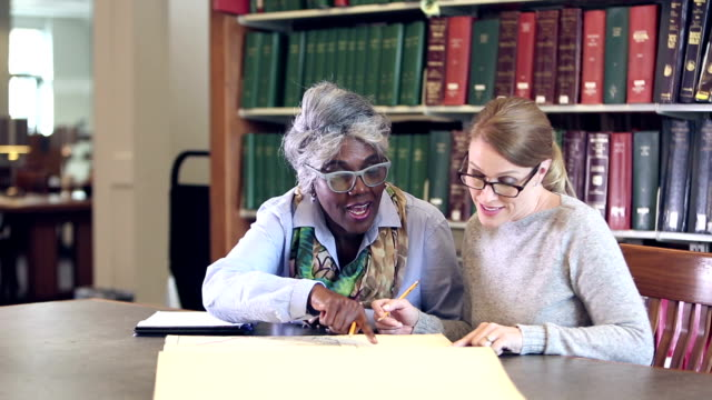 women doing research together in library, with big book - post secondary education stock videos & royalty-free footage