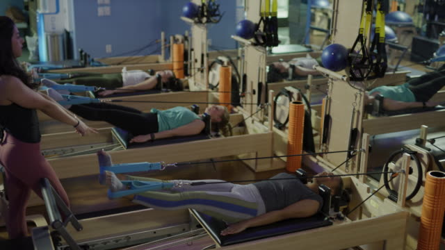 women doing resistance training with legs apart laying on pilates reformer exercise machine / lehi, utah, united states - legs apart stock videos and b-roll footage