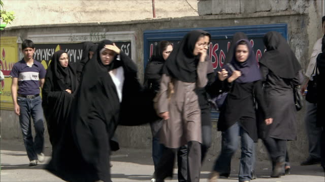 vídeos de stock, filmes e b-roll de ws women dressed in hijabs walking up and down street, shiraz, iran - irã