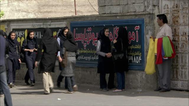 ws women dressed in hijabs walking up and down street, shiraz, iran - 中東点の映像素材/bロール