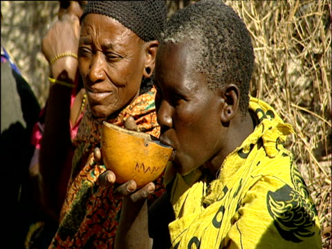 Women drink water from large gourd Dodoma region Tanzania