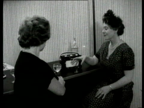 women drinking alcohol and listening to portable radio / close shots of radio being tuned women listening to radio on august 23 1960 in london - radio stock videos & royalty-free footage