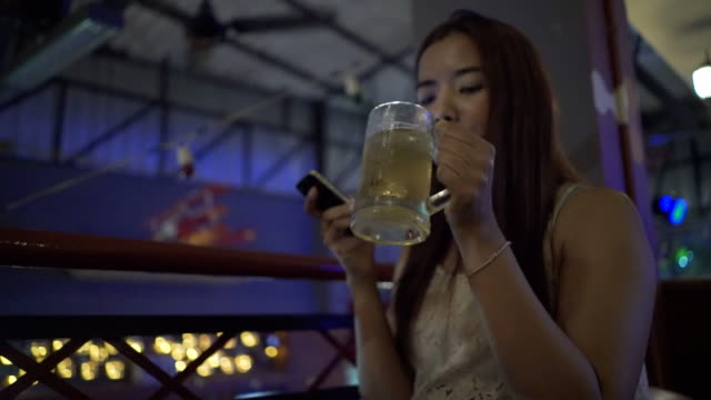 Women drinking beer and use smartphone